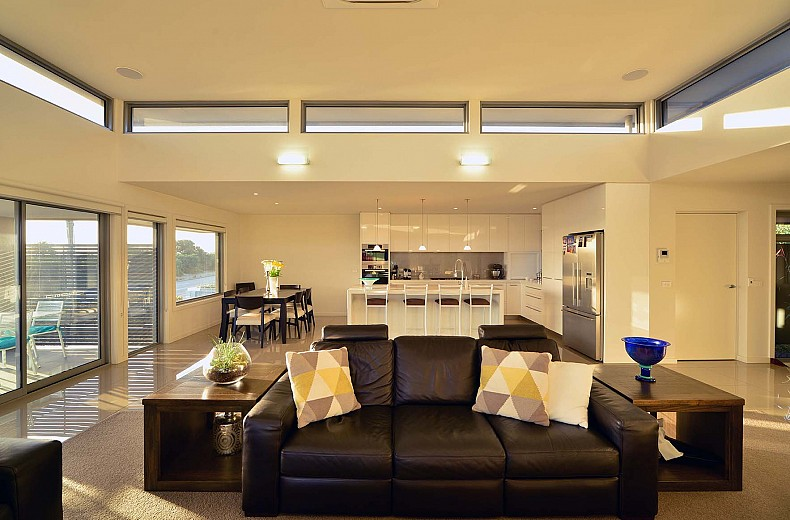 The living area with kitchen and dining behind, raised central roof with 360 degree highlight windows floats above.